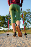 Nordic walking in summer. Closeup of man's legs with nordic walking poles Stock Image