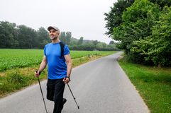 Nordic walking training in nature. Active athletic man walking outdoors with hiking stick on a sommer day Royalty Free Stock Photo