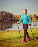 Nordic walking. Vintage retro effect filtered hipster style image of nordic walking adventure and exercising concept - woman hiking with nordic walking poles in stock image