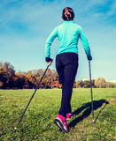 Nordic walking. Vintage retro effect filtered hipster style image of nordic walking adventure and exercising concept - woman hiking with nordic walking poles in royalty free stock photo
