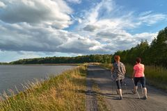 Nordic Walking - a walk with two women`s poles along the lake stock images