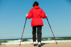 Nordic walking. Woman hiking on the beach. Royalty Free Stock Photography