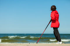 Nordic walking. Woman hiking on the beach. Stock Photos