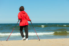 Nordic walking. Woman hiking on the beach. Stock Images