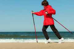 Nordic walking. Woman hiking on the beach. Stock Photo
