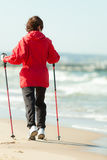 Nordic walking. Woman hiking on the beach. Royalty Free Stock Images