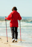 Nordic walking. Woman hiking on the beach. Stock Photography