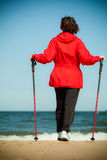 Nordic walking. Woman hiking on the beach. Royalty Free Stock Photo
