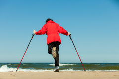 Nordic walking. Woman hiking on the beach. Stock Photo