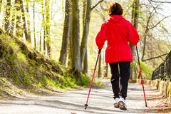 Nordic walking. Woman hiking in the forest park. Stock Photography