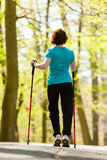 Nordic walking. Woman hiking in the forest park. Royalty Free Stock Image