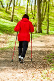 Nordic walking. Woman hiking in the forest park. Royalty Free Stock Photo