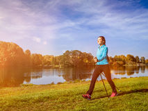 Nordic walking woman outdoors. Nordic walking adventure and exercising concept - woman hiking withnordic walking poles in park. With light leak and lens flare Royalty Free Stock Photography