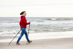 Nordic walking - young girl working out on beach Royalty Free Stock Photography