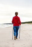 Nordic walking - young girl working out on beach Stock Image