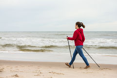 Nordic walking - young girl working out on beach Stock Photos