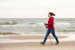 Nordic walking - young girl working out on beach Royalty Free Stock Photos