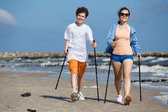 Nordic walking - young people working out on beach Stock Photography