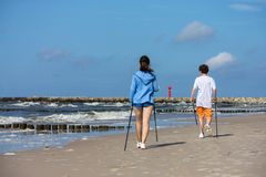 Nordic walking - young people working out on beach Stock Photos