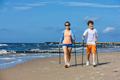 Nordic walking - young people working out on beach Royalty Free Stock Image