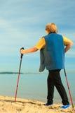 Nordico senior della donna attiva che cammina su una spiaggia Da dietro Fotografie Stock Libere da Diritti