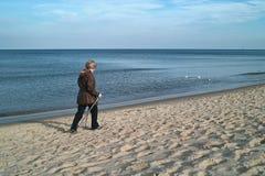 Nordisches Gehen der Frau auf Strand Lizenzfreies Stockfoto