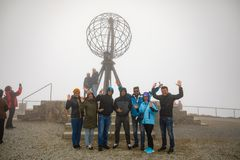 Nordkapp, Norway - 26.06.2018: Group of tourists keep coming to the famous north cape and love to take photos with the royalty free stock photography