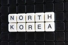 Nordkorea-Textwortkreuzworträtsel Alphabetbuchstabe blockiert Spielbeschaffenheitshintergrund Weiße alphabetische Buchstaben auf  Lizenzfreies Stockbild