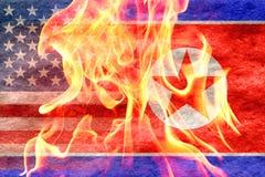 Nordkoreanische Flagge, die in amerikanische Flagge mit Feuer in der Front verblaßt Lizenzfreie Stockbilder