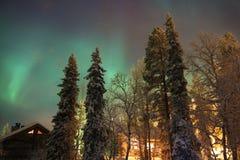 Nordlichter über den Kiefern und den Kabinen Lizenzfreie Stockfotografie