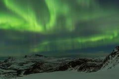 Nordlichter über Schnee bedeckten Berge bei entferntem Norwegen Co Stockfotos