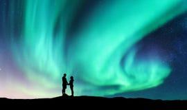 Nordlichter und umarmen Paare auf dem Hügel Stockfoto
