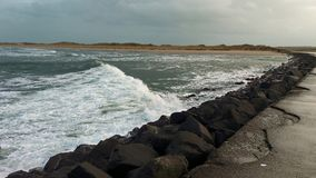 Nordlig Castlerock - Irland Härlig havvåg som bryter på bakgrunden av land arkivbilder