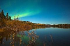 Nordliga lampor och fallfärger på den lugnaa laken Royaltyfri Bild