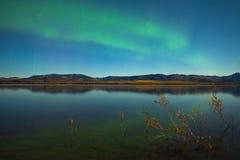 Nordliga lampor och fallfärger på den lugnaa laken Arkivfoton