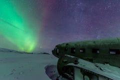 Nordliga ljus över den plana haveriet på haveriet sätter på land i Vik, Island royaltyfri fotografi