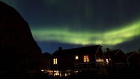Nordliga ljus över kojor i Hamnoy Arkivbild