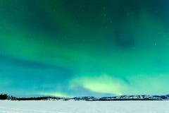 Nordliga ljus över månen tände den djupfrysta sjön Laberge Fotografering för Bildbyråer