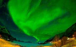 Nordliga ljus skiner ljust och härligt ovanför skarpa maxima och sjöar av Lofoten berg Royaltyfri Fotografi