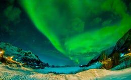 Nordliga ljus skiner ljust och härligt ovanför skarpa maxima och sjöar av Lofoten berg Royaltyfri Foto