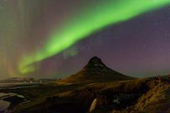 Nordligt ljus över sikt för natt för Kirkjufell vulkanberg fotografering för bildbyråer