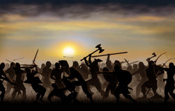 Nords. Silhouettes fighting warriors are seen against the background of the rising sun Royalty Free Stock Image