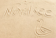 Nordsee and seagull drawn in beach sand Royalty Free Stock Photography