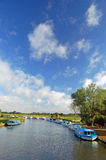 The Norfolk Broads, England. A tranquil flat summer landscape, big skys and wide horizons, and a string of holiday cruisers berthed by the waterway ~ A typical stock images