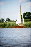 Norfolk Broads sail boat on a river by the bankment Stock Image