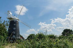 Norfolk coastline blue sky background with a windmill in the middle Stock Image