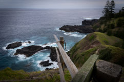 Norfolk Island Vista - Two Chimneys. Vista from Two Chimneys on Norfolk Island with the fence leading off the cliff to the rocks and rough water below, Norfolk royalty free stock photos
