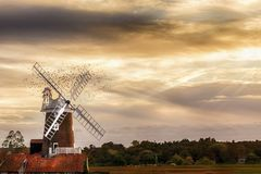 Norfolk windmill with flock of birds at sunset. Cley Windmill is a grade II listed five storey tower mill located on the North Norfolk coast dating from the 18th Stock Image