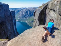 Norge - en flicka som ligger p? kanten av ett brant berg som l?tsar f?r att vara flyg fotografering för bildbyråer