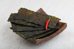 Nori seaweed sheets. Spicy Nori seaweed sheets with pepper on wood stock image